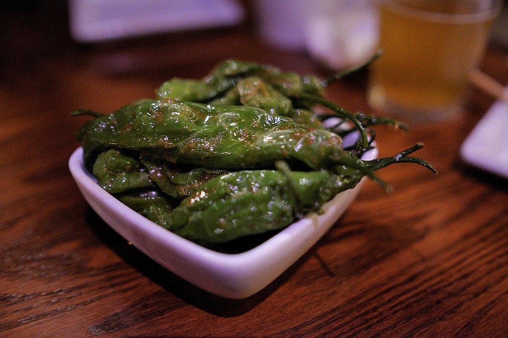 Shishito peppers are roasted to reduce spice slightly and then slathered in garlic paste.