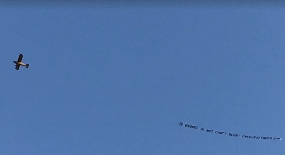 """Funded by San Diego brewers and fans, an airplane tows a banner over the opening block party for 10 Barrel's east village brewpub, declaring """"10 Barrel is not craft beer!"""""""