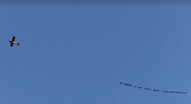 "Funded by San Diego brewers and fans, an airplane tows a banner over the opening block party for 10 Barrel's east village brewpub, declaring ""10 Barrel is not craft beer!"""