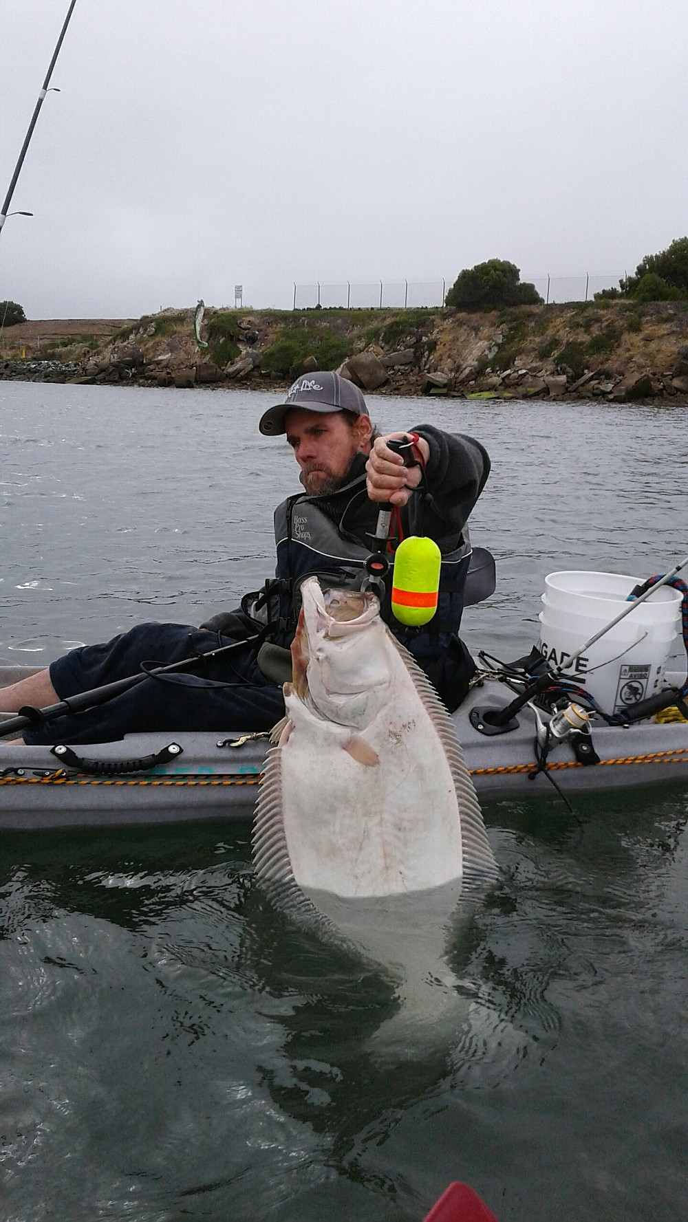 A shot of a friend Chris with a nice 15-pound halibut from off the poles at the seaplane ramps.