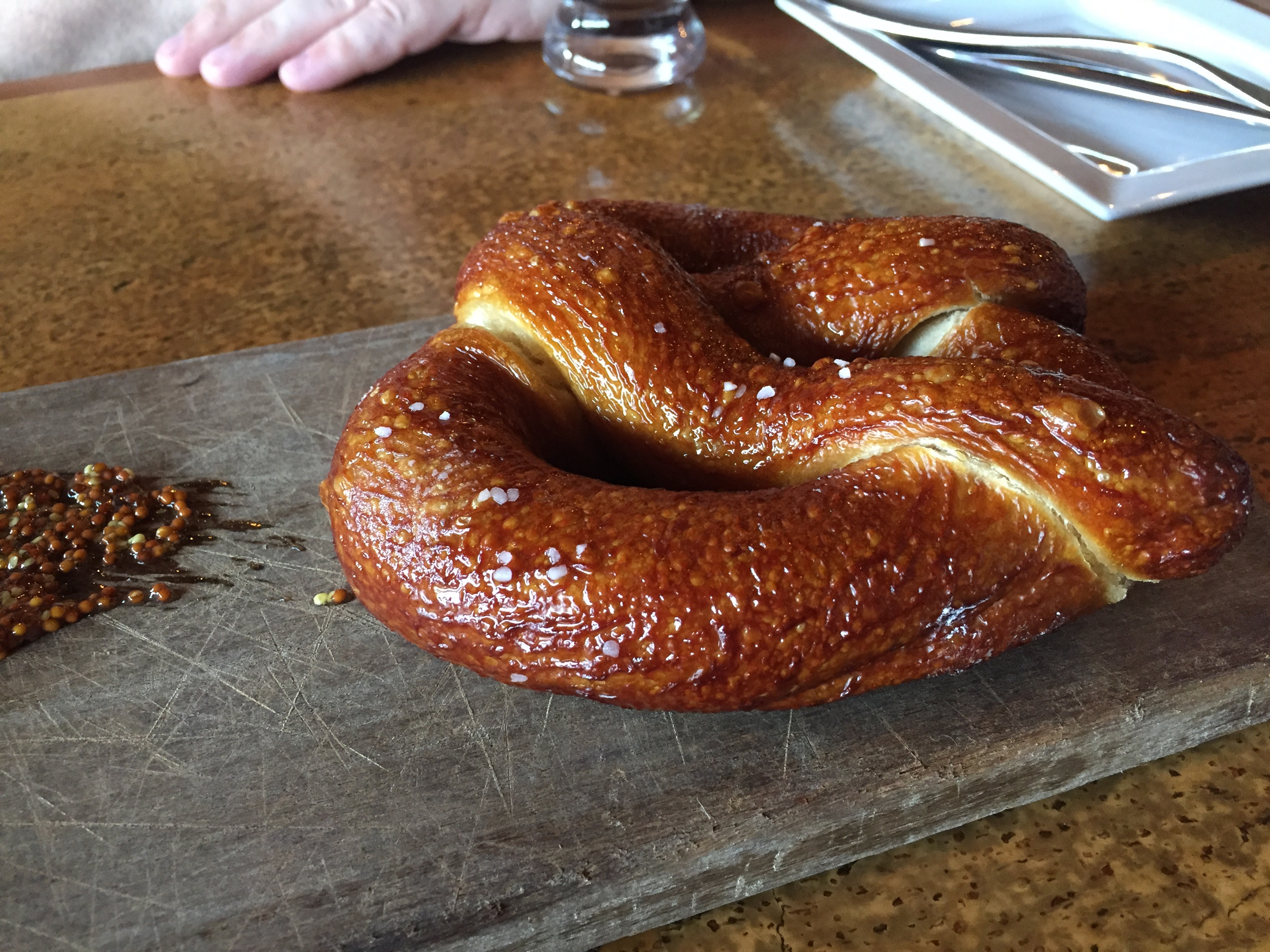 Bavarian pretzel, served with cheese fondue and mustard seed.