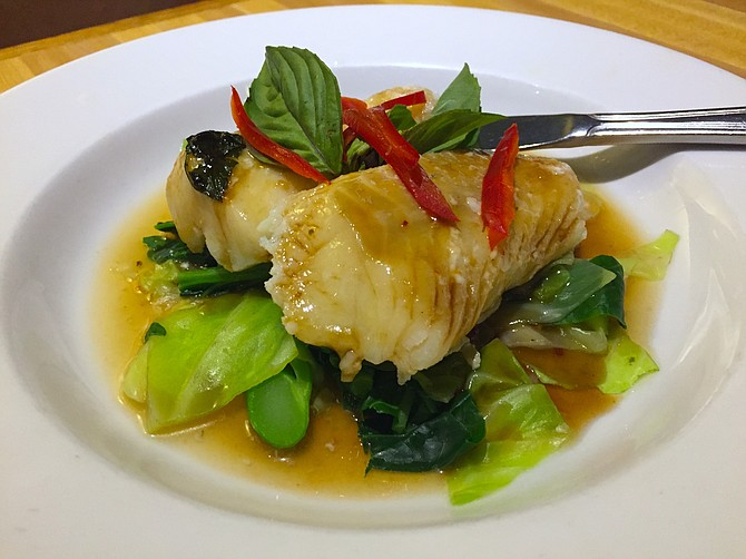 Steamed cod over bok choy in a spicy lime-garlic broth, garnished with peppers and mint leaves