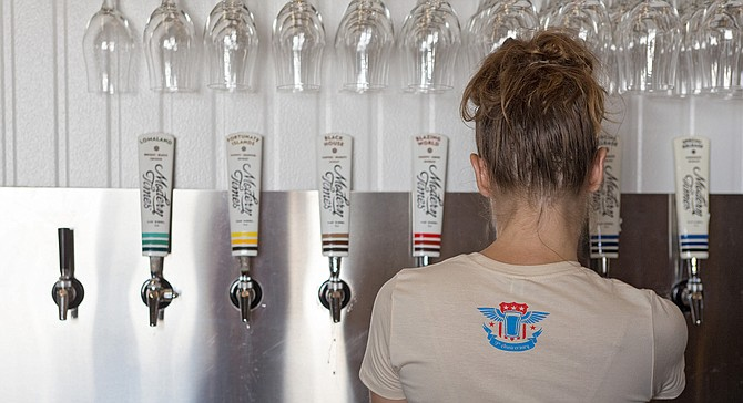 A Modern Times employee pours beer in its Point Loma tasting room.