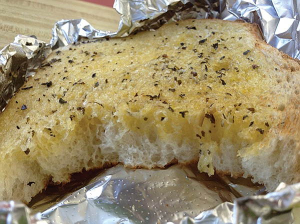 Big, thick, hot chunk with a quarter-inch of soaked butter and garlic, plus basil sprinkled on top.