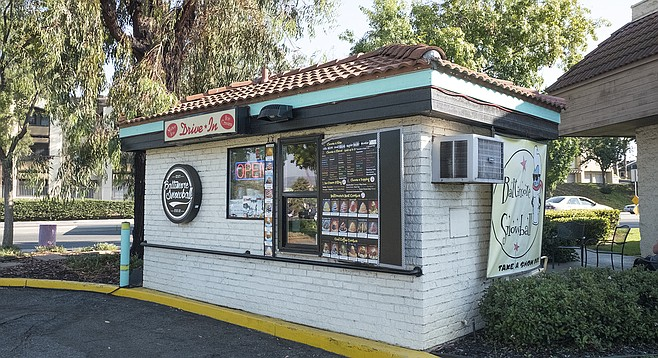 A small drive-thru shack in a strip mall serving unusual ice treats