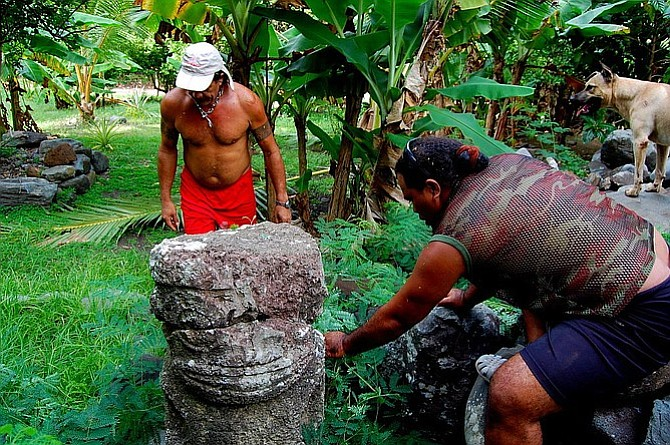 From left to right: Harris, Romain and Ganja inspect the large stone tiki at Hakamoui, Ua Pou.