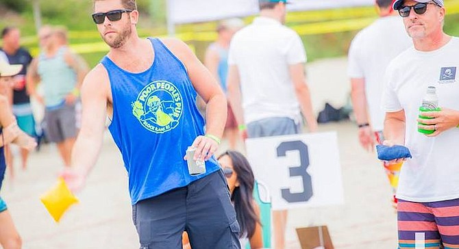 Even at the American Cornhole Championships, players commonly have a beer in one hand. - Image by Chris Brake