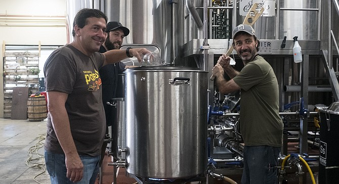 AleSmith owner Peter Zien adds hops to a collaboration beer with Second Chance head brewer Marty Mendiola (right) and assistant brewer Craig Gregovics.
