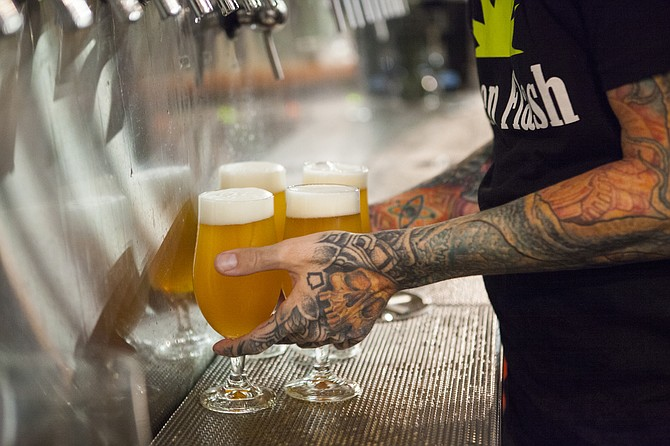 An employee pours Green Flash beer