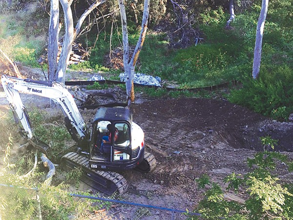 Backhoe driver moves fallen tree