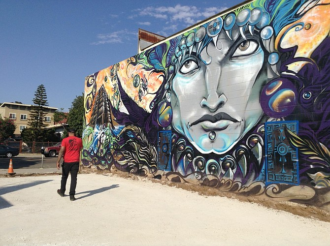 Shawn Buss walks across the spare lot where the patio cafe will go. Mural comes with the property