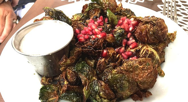 Fried Brussels Sprouts covered in fresh pomegranate seeds and served beside a heaping portion of tangy and spicy yogurt