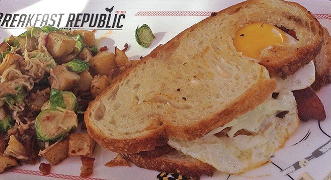 "Breakfast Sammie. Comes with ""Jurassic pork bacon, tomato, herb spread, eggs sunny side up, sourdough bread, house potatoes."""