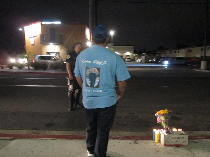 """I raised him from a baby.""  Uncle still in mourning after eight years stands by street memorial wearing teeshirt dedicated to the victim."