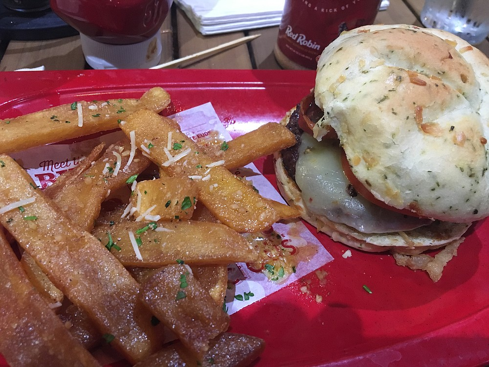 The A-1 Peppercorn burger comes with bacon, pepper jack, peppercorn spread, tomatoes, and deep-fried onions on an undercooked bun.