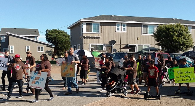 Rafael Bautista (left, red cap) leading Village Apartments tenants and activists on a march, September 29