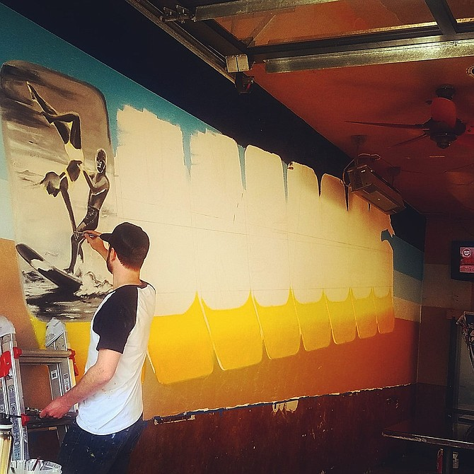 Jake Stricker working on the new mural