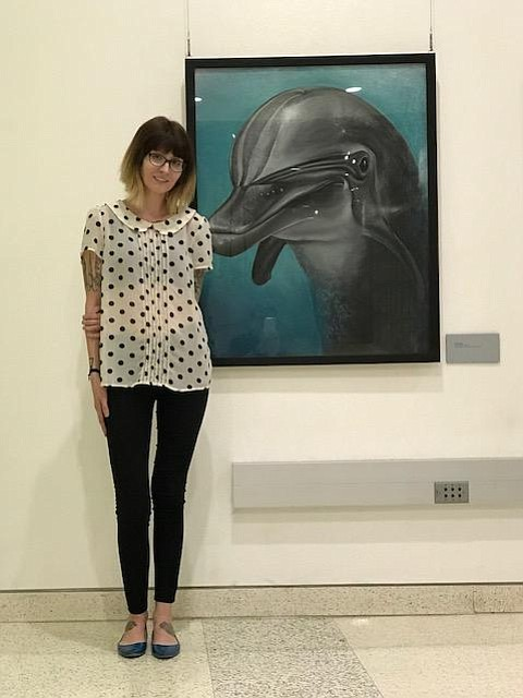 "Lisa Korpos poses with ""Spree,"" a dolphin portrait she painted"