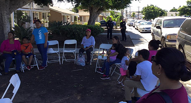 Tenants locked out of the Village Apartments rental office wait to meet with management under police supervision. Photo: San Diego Tenants United