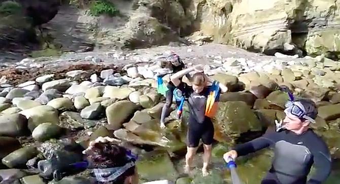 Jet Ski unit rescues 3 uninjured people from Devil's Slide rocks and transports them to La Jolla Shores.