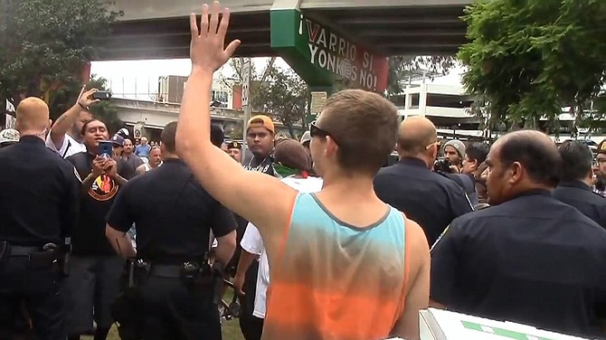 Surrounded by police protection one patriot picnic-goer waves to the crowd pressing in against him.