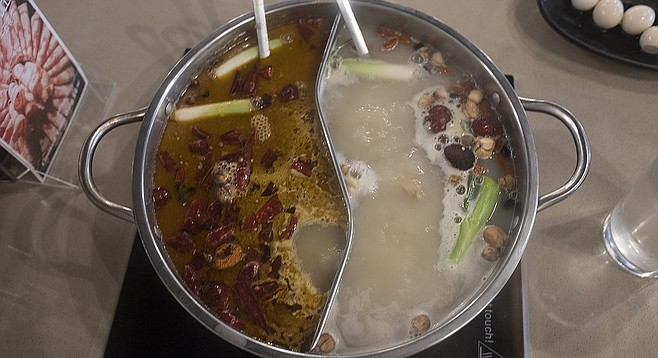 A yin-yang shaped hot pot allows diners to try both regular and spicy broths.