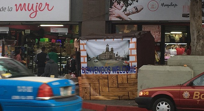 The straight lines of the framed tarps make this vendor's stand blend with the façade and sidewalk-scape.