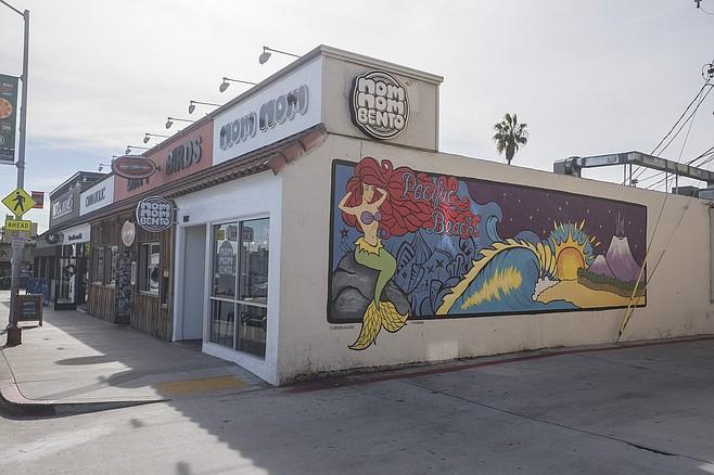 A mural decorates little counter shop Nom Nom Bento
