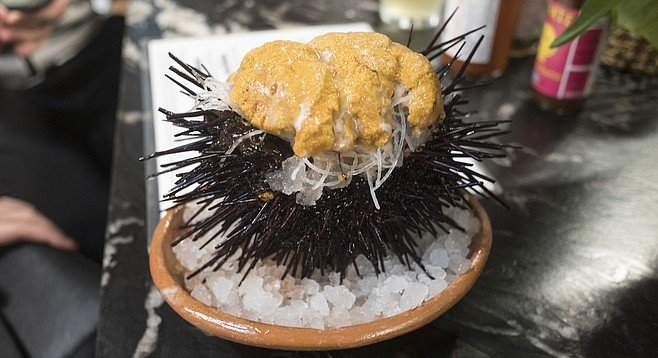 A healthy portion of sea urchin roe, serve in its quivering, spiny shell.