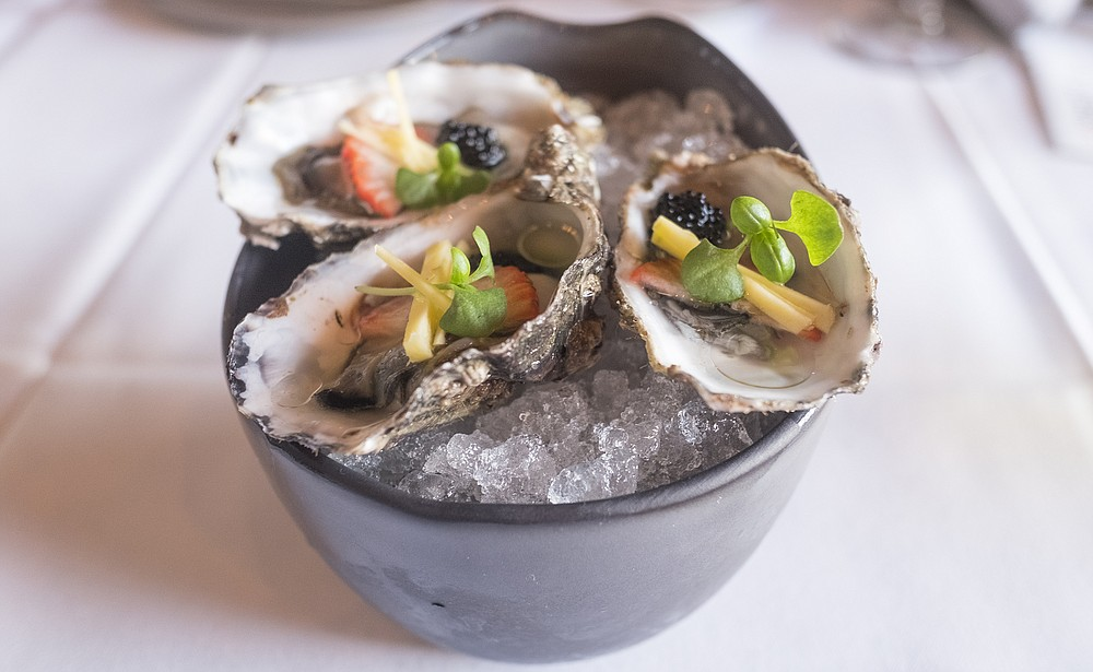Raw oysters topped with fruit, micro-basil, and caviar