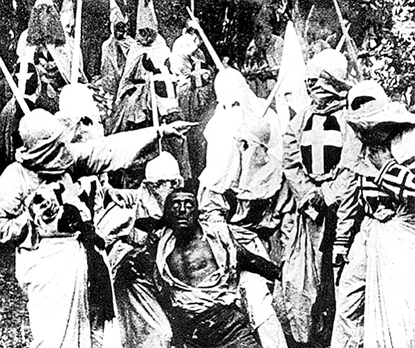 Hooded Klansmen catch Gus, portrayed in blackface by actor Walter Long in The Birth of a Nation.