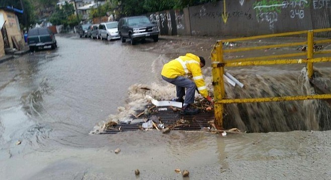 A city worker attempts to clear a storm-drain grate