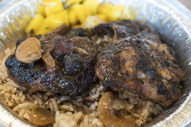 Jerk chicken (right) and oxtail (with a butter bean on top), with mangos.