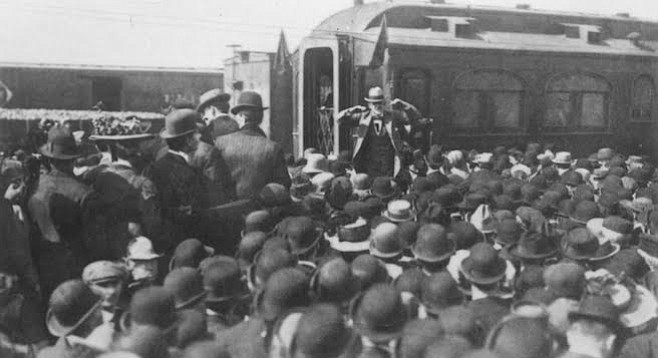 Eugene Debs speaking before a crowd next to a Pullman train car, the manufacturer of which was a strike target due to unfair treatment of workers.
