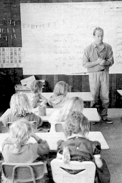 Jacques Moiroud stands in front of his class of kindergartners and first graders. In France the tradition is for men, not women, to teach the younger grades.