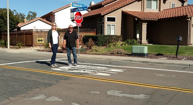 Claudia Walker and neighbor Bob Camacho stand near an area of patched road on Scripps Trail.