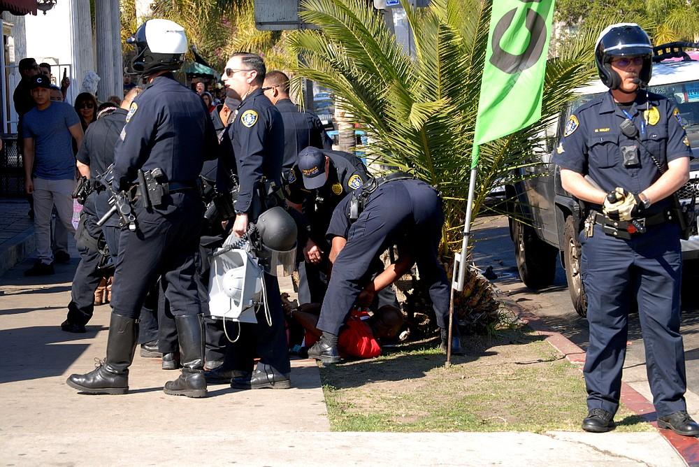 A man was taken down by several policemen.