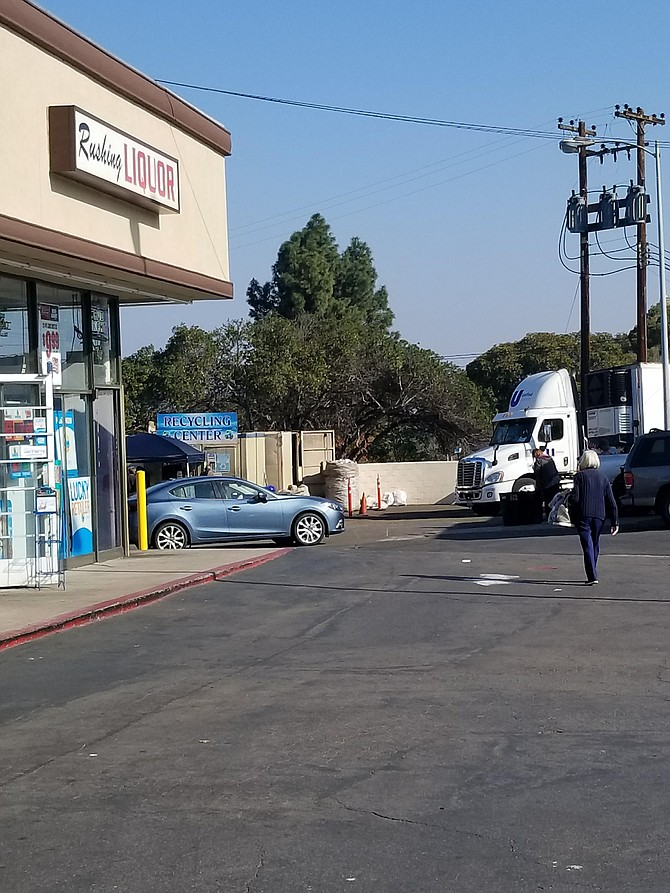 Cars and semi-trucks try to dodge recyclers in the small area it occupies (there is a driveway that comes up thru the recycling center)