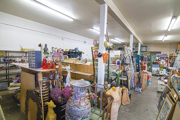 Windmill thrift shop: statue of a seated doberman, duffle bag with raggedy Barbie dolls and VHS movies; dishes, vases, dressers, and a heavy metal rhino head wall-hanging.