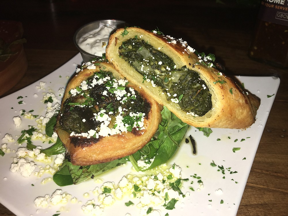 The spanakopita is a pocket sandwich made with crispy puff pastry and filled with a lemon-tinged spinach and feta cheese.