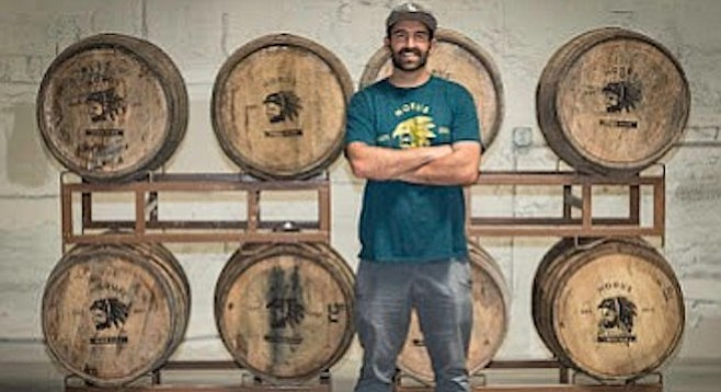 Brewer Kyle Harrop stands before a rack of barrels at his brewery, Horus Aged Ales