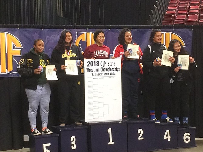 Madlyne Navarro standing on number 3 receives her medal at state championships
