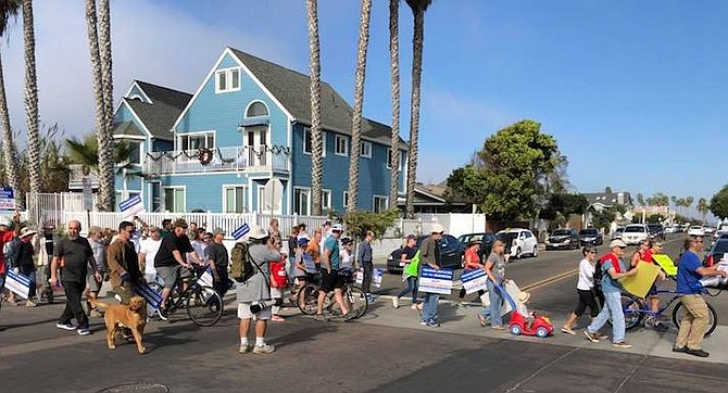 Protestors walking past illegal vacation rentals in a November protest in Ocean Beach