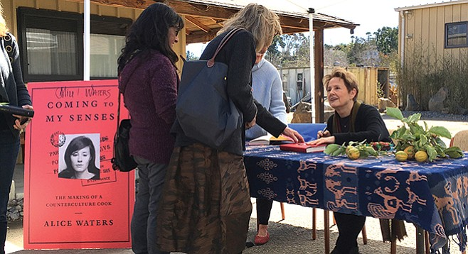 Alice Waters then (on the book cover) and now (at the table)