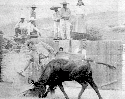 John Wayne peeks out from behind post as Boetticher demonstrates guiding a bull with a muleta.