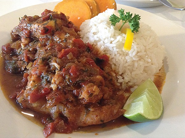 Tilapia under a sauce of tomatoes, onions, spices, fish paste, and parsley.