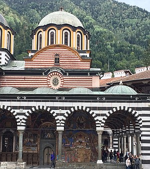 Church of the Nativity at Rila Monastery with mountains looming in the background.