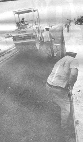 Close to 11:00 a.m., the concrete paver rolls slowly past Daley's asphalt paver.