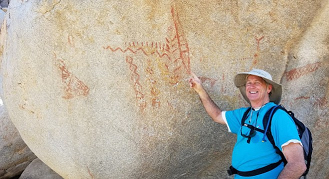 A hiker points out the mysterious pictographs