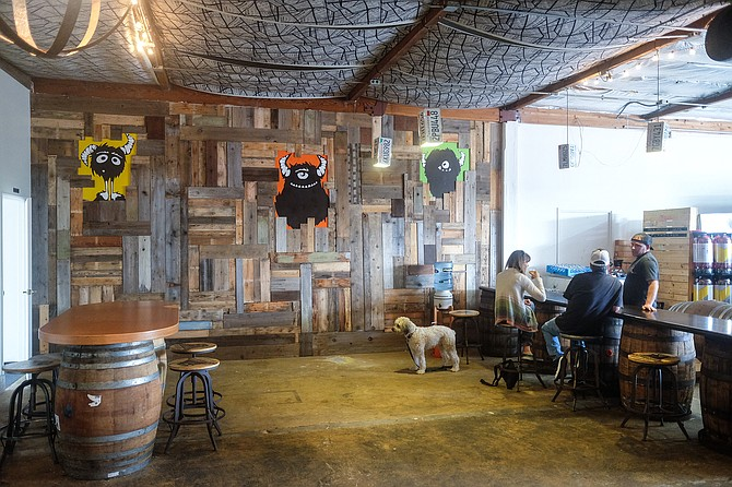 Brewer Cameron Pryor engages with customers, while a dog watches the door.